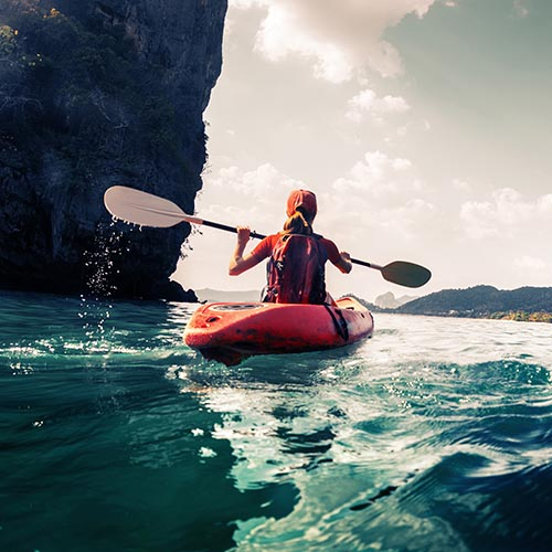 Kayaker passing a looming cliff